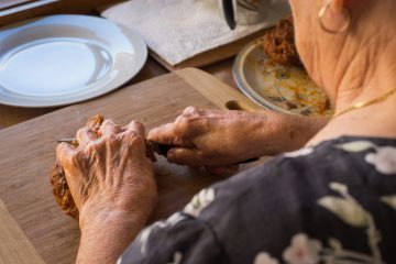 Grandmother's hands cutting meat