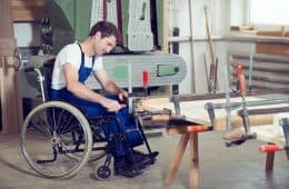 man in wheelchair in carpenter workshop