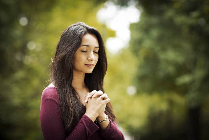 Woman with hands clasped in prayer outdoors - Prayer and meditation