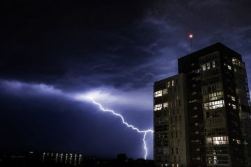 Lightning striking near tall building