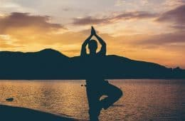 Man doing yoga on beach at sunset