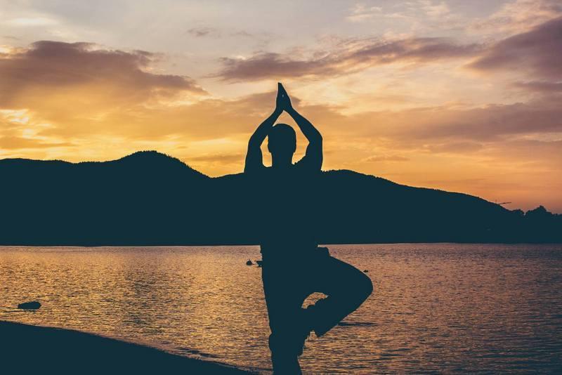 Man doing yoga on beach at sunset