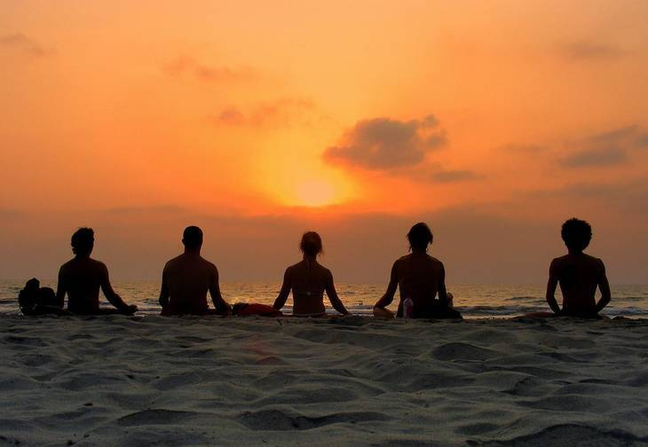Five people sitting on beach at sunset - Conscious awareness