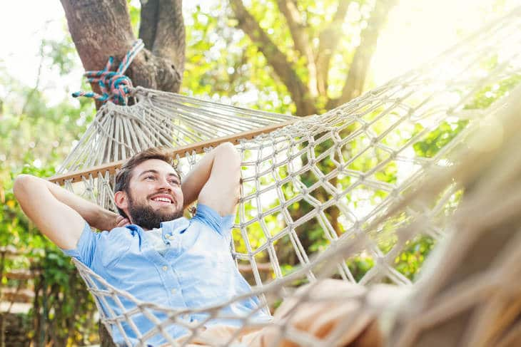 Young man relaxing in hammock - Sin or virtue