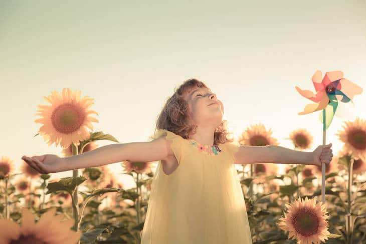 Blissful little girl with sunflowers - Teaching mindfulness to kids