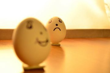 Egg with happy face and egg with sad face - Acceptance of negativity