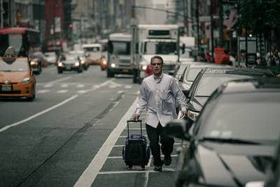 Man hurrying suitcase down busy street - The joke's on you
