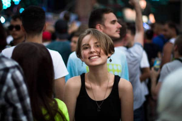 Closeup of smiling young woman in crowd - The death of identity
