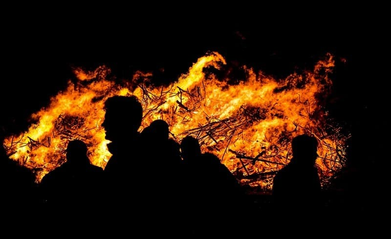 People next to a huge fire at night