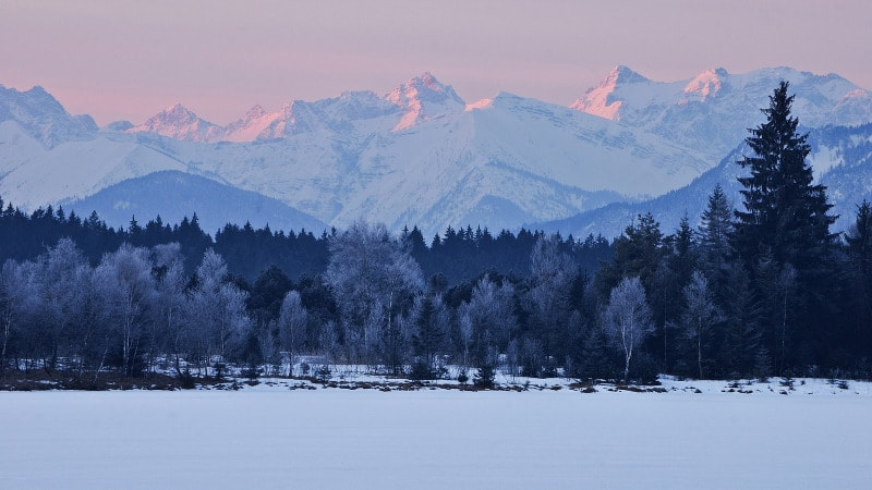 Landscape photo of mountains covered in snow at sunset