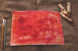 Bright pink blank canvas with brushes and oils lying next to it