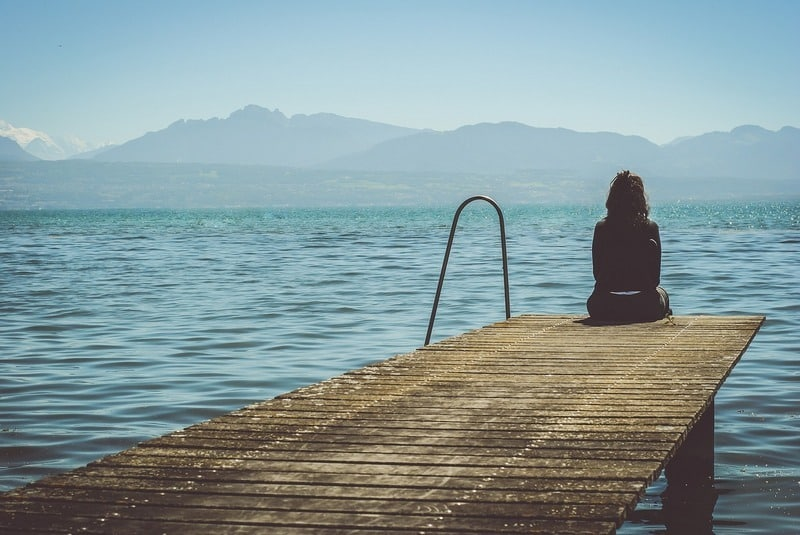 Woman sitting alone on the end of a pier on a lake