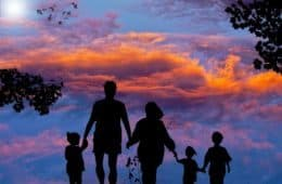 Parents and children holding hands watching the sun set
