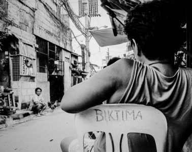 Woman sitting on a chair with the word 'victim' on the back written in Tagalog