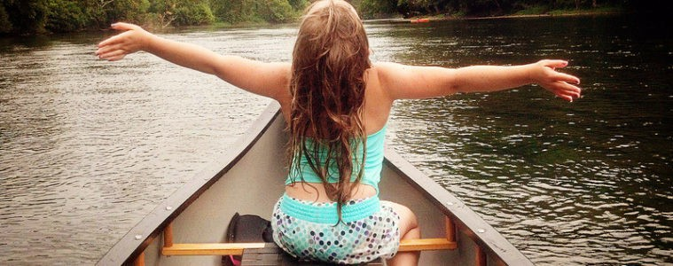 Young girl with arms wide open sitting in a canoe on a lake