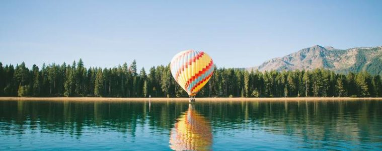 Hot air balloon floating just above lake - Liberation in wanting