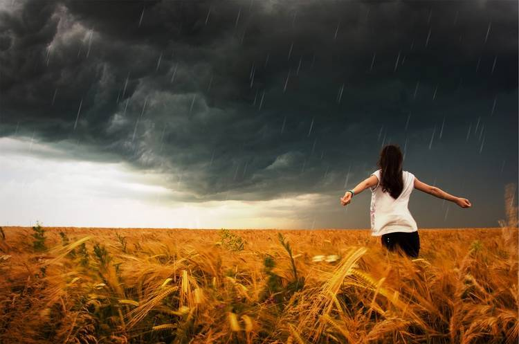 Woman with arms outstretched in stormy weather - Liberation in wanting
