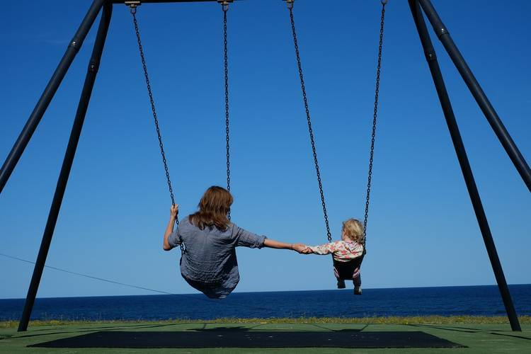 Parent and young child holding hands on swings at park - Meaningful parenting