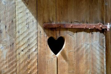 Old wooden door with small heart cut in it - The meaning of compassion