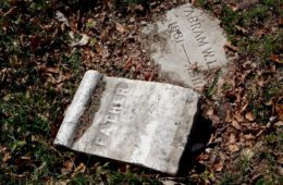 "Tombstone lying in grass with word ""Father"""