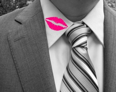 Man in a suit with lipstick on his collar