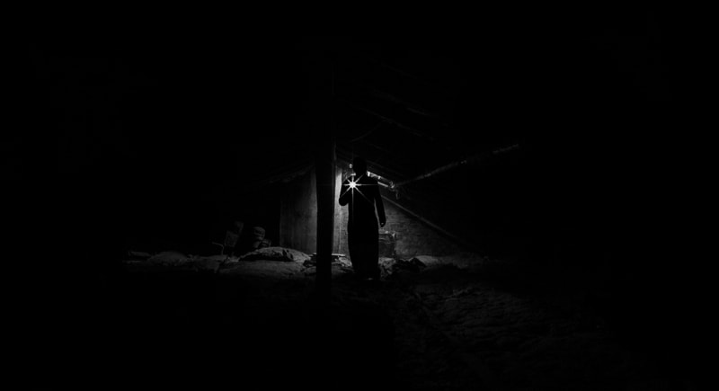 Man with flashlight in dark mine