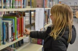Female child in front of library bookshelf - Daycare dropout