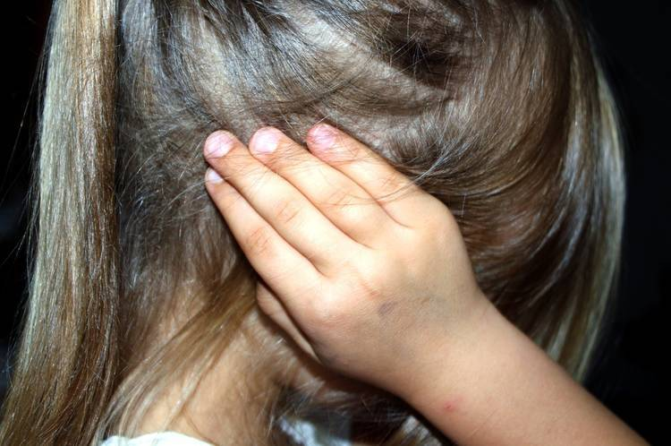 Upset child putting hands over her ears - Confronting reality
