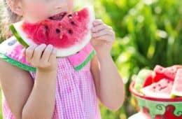 Little girl taking bite of watermelon - How to satisfy young fussy eaters