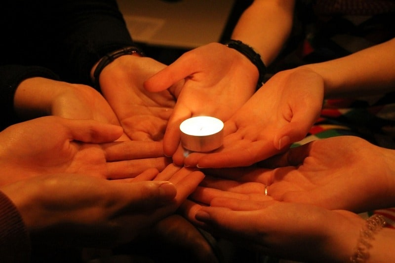 circle of hands holding candle