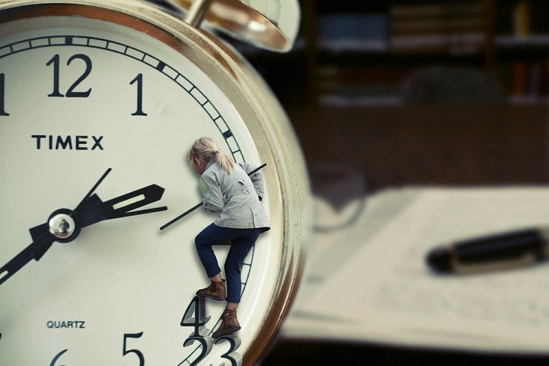 woman hanging on to he second hand of a clock