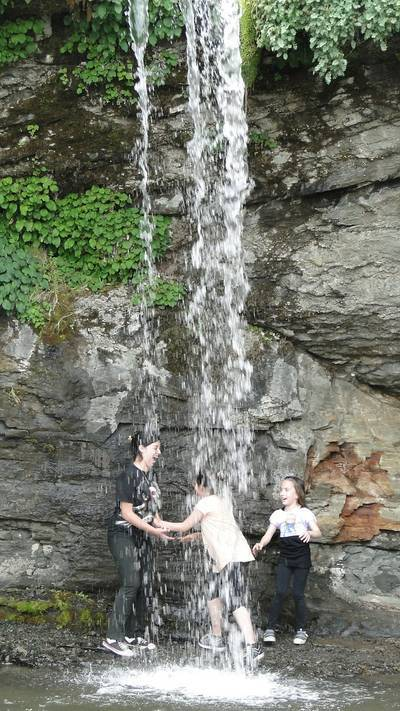 Three children dancing under waterfall - Poems by Woven Green