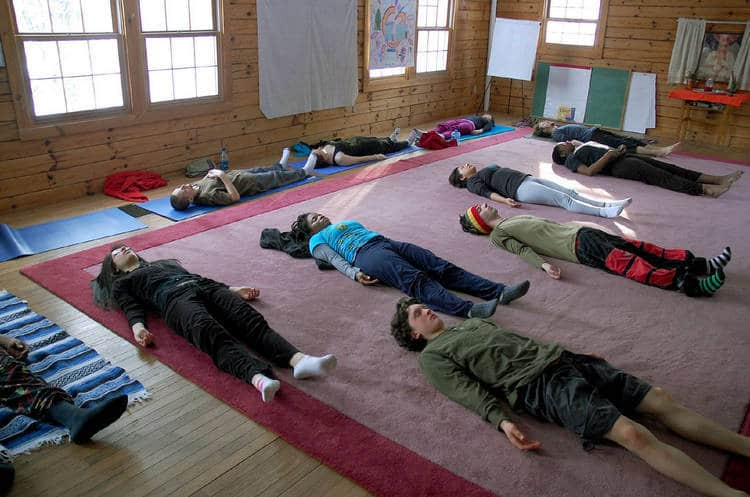 People relaxing in savasana during Yoga class - Psychological & spiritual therapy