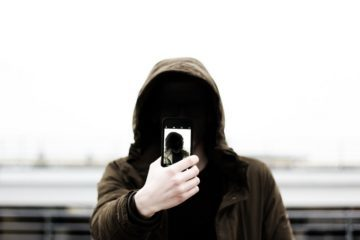 man in hoodie with selfie on a phone