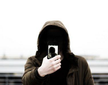 man in hoodie with selfie on a phone