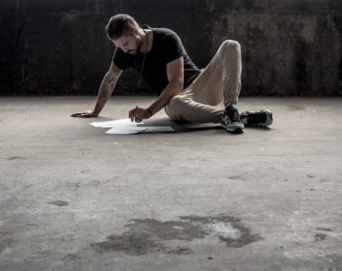 Man sitting on cement floor writing - Healing words