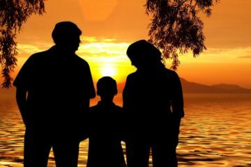Father and mother holding hands with son at sunset