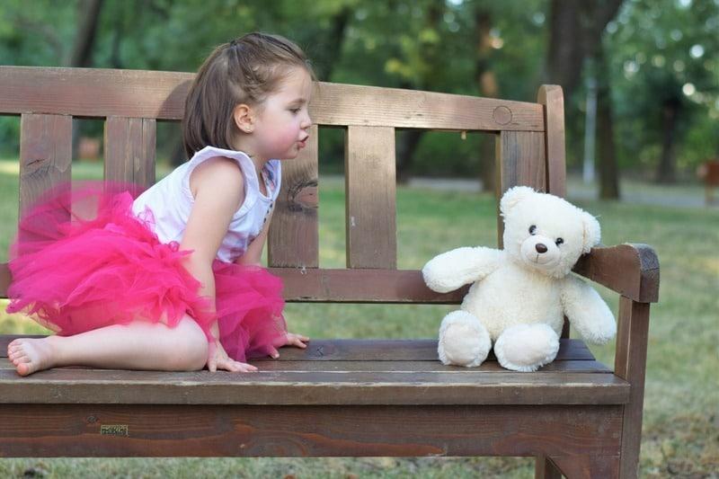little girl talking to teddy bear