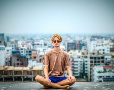 young man sitting on top of building meditating