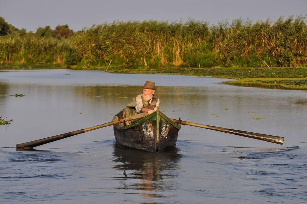 old man in rowing boat on river