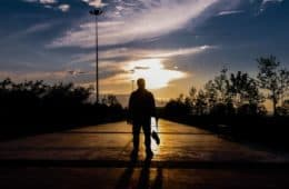 Man standing on boulevard at sunset - Poems by Mike Larcombe