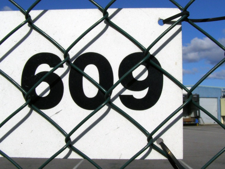 Number 609 on a piece of metal attached to fence