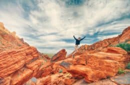 Young woman joyfully climbing rocks - The energy of yes