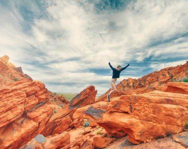 Young woman joyfully climbing rocks - The energy of yes