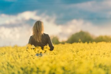 Woman standing in field of yellow flowers looking at trees and sky - Poems by Sherin Shefik