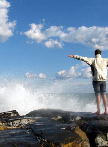Man stretching his arms out wide next to water - The science of freedom