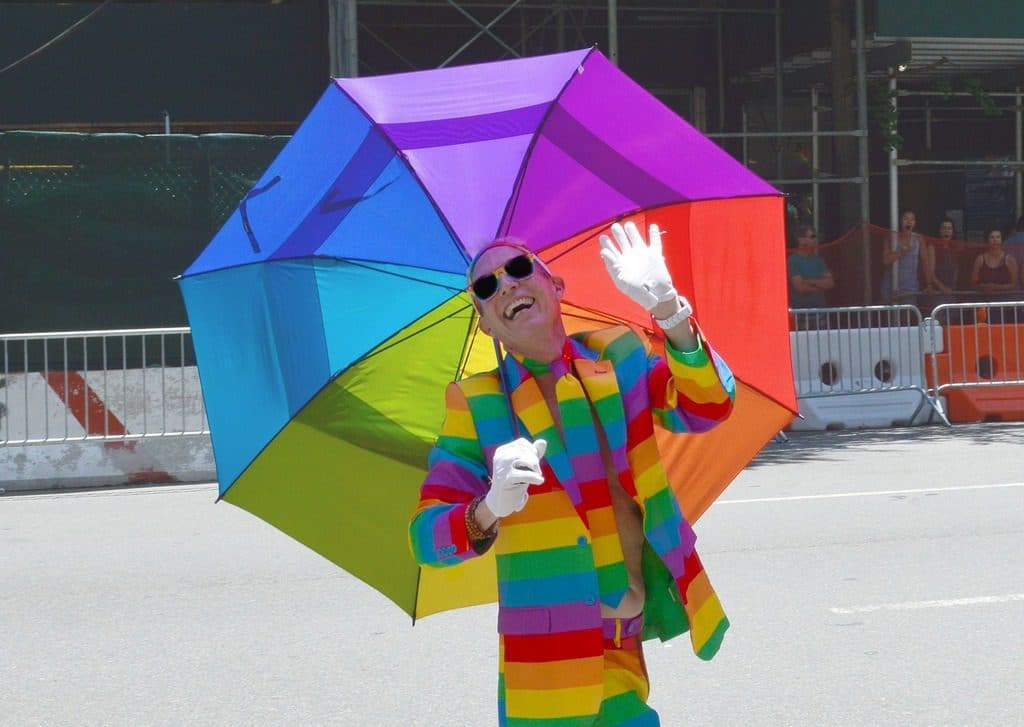 gay person with umbrella in lgbt rainbow colours