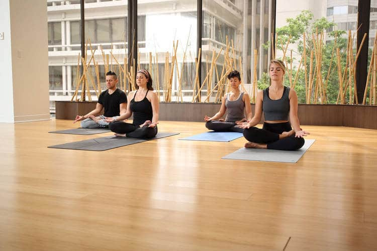 Four people doing breathing exercise in Yoga class - Ujjayi breathing technique