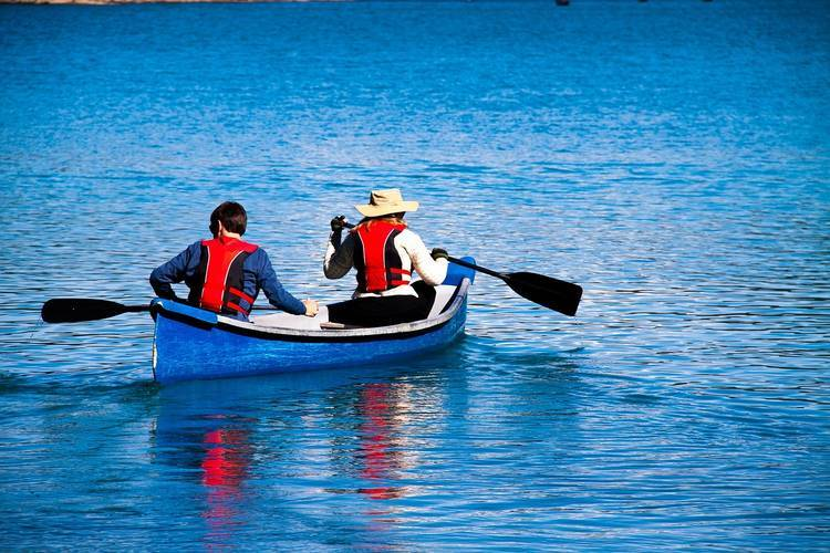 Man and woman paddling in blue canoe on lake - Philbin Pond