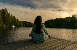 Woman meditating on dock outdoors - Ujjayi breathing technique